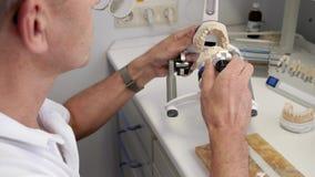 Ο οδοντικός τεχνικός eyeglasses με τη βούρτσα επισύρει την προσοχή την άσπρη σκόνη στα κεραμικά δόντια κατόπιν παρεμβάλλει στις ε φιλμ μικρού μήκους