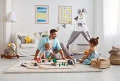 Ο οικογενειακοί πατέρας και τα παιδιά παίζουν έναν σιδηρόδρομο παιχνιδιών στο χώρο για παιχνίδη στοκ φωτογραφίες