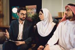 Ο οικογενειακός θεράπων στο γραφείο βοηθά το αραβικό ζεύγος στοκ φωτογραφίες