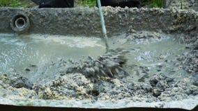 Ο οικοδόμος αναμιγνύει το συγκεκριμένο ασβεστοκονίαμα με τον ηλεκτρικό αναμίκτη Μίξη της άμμου και του τσιμέντου o απόθεμα βίντεο