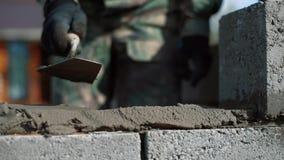 Ο οικοδόμος βάζει ένα μίγμα τσιμέντο-άμμου για την περαιτέρω τοποθέτηση του φραγμού απόθεμα βίντεο