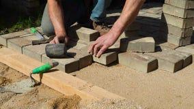 Ο οικοδόμος βάζει τις πέτρες επίστρωσης φιλμ μικρού μήκους