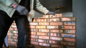 Ο οικοδόμος βάζει το τούβλο Ένας εργάτης οικοδομών βάζει έναν τουβλότ απόθεμα βίντεο