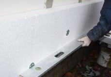 Ο οικοδόμος εγκαθιστά Styrofoam τον πίνακα μόνωσης Μόνωση πολυστυρολίου τοίχων σπιτιών στοκ εικόνες