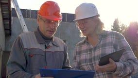 Ο οικοδόμος και ο αρχιτέκτονας στο κράνος συζητούν την κατασκευή σύμφωνα με το πρόγραμμα σχεδίων απόθεμα βίντεο