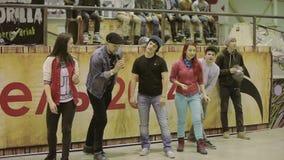 Ο οικοδεσπότης στο καπέλο με το μικρόφωνο δίνει την έναρξη στα κορίτσια, αγόρια για το τρέξιμο Ανταγωνισμός στο skatepark παιχνίδ απόθεμα βίντεο