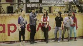 Ο οικοδεσπότης στο καπέλο με το μικρόφωνο δίνει την έναρξη στα κορίτσια, αγόρια τρέξιμο Ανταγωνισμός στο skatepark πρόκληση απόθεμα βίντεο