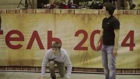 Ο οικοδεσπότης στο καπέλο με το μικρόφωνο δίνει την έναρξη στο αγόρι δύο για το τρέξιμο Ανταγωνισμός στο skatepark παιχνίδι απόθεμα βίντεο