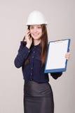 Ο οικοδόμος στην ομιλία αλλά το τηλέφωνο κρανών με έναν φάκελλο δίνει Στοκ φωτογραφία με δικαίωμα ελεύθερης χρήσης