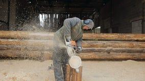Ο οικοδόμος χειρίζεται το ξύλινο αλυσιδοπρίονο ξυλείας Στο κλίμα είναι μέρος του μέλλοντος του σπιτιού φιαγμένου από ξύλινες ακτί φιλμ μικρού μήκους