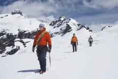 Οδοιπόροι που ενώνονται από τη γραμμή ασφάλειας στα χιονώδη βουνά Στοκ εικόνα με δικαίωμα ελεύθερης χρήσης