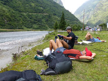Οδοιπόροι που χαλαρώνουν κοντά στον ποταμό στο χωριό Tal στο Νεπάλ Στοκ Εικόνες