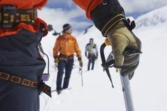 Οδοιπόροι που χρησιμοποιούν τα ραβδιά περπατήματος στα χιονώδη βουνά Στοκ φωτογραφίες με δικαίωμα ελεύθερης χρήσης