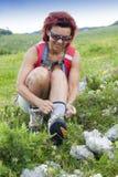 Οδοιπόρος γυναικών που δένει τα κορδόνια στα βουνά Στοκ Φωτογραφίες