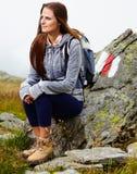 Οδοιπόρος γυναικών που στηρίζεται σε έναν βράχο Στοκ φωτογραφία με δικαίωμα ελεύθερης χρήσης