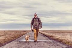 Οδοιπόρος και σκυλί που περπατούν στο δρόμο Στοκ Φωτογραφίες
