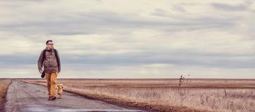 Οδοιπόρος και σκυλί που περπατούν στο δρόμο Στοκ Φωτογραφία
