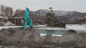 Οδοιπόρος κοριτσιών που στέκεται στο βράχο στην όχθη ποταμού και που κοιτάζει γύρω Χειμώνας, καλυμμένο βουνά χιόνι, γέφυρα αναστο απόθεμα βίντεο