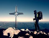 Οδοιπόρος μεγάλο crucifix στην αιχμή βουνών Σταυρός σιδήρου στην κορυφή βουνών Άλπεων Στοκ Εικόνες