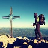 Οδοιπόρος μεγάλο crucifix στην αιχμή βουνών Σταυρός σιδήρου στην κορυφή βουνών Άλπεων Στοκ φωτογραφία με δικαίωμα ελεύθερης χρήσης