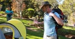Οδοιπόρος με το σακίδιο που εξετάζει την πυξίδα στην επαρχία φιλμ μικρού μήκους