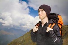 Οδοιπόρος με το σακίδιο πλάτης που περπατά κατά μήκος μιας έκτασης βουνών στοκ εικόνα