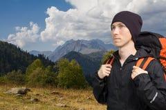 Οδοιπόρος με το σακίδιο πλάτης που περπατά κατά μήκος μιας έκτασης βουνών στοκ εικόνα με δικαίωμα ελεύθερης χρήσης