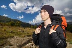 Οδοιπόρος με το σακίδιο πλάτης που περπατά κατά μήκος μιας έκτασης βουνών στοκ φωτογραφίες