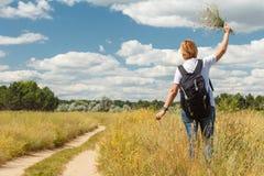Οδοιπόρος με το σακίδιο πλάτης που περπατά στον αγροτικό δρόμο Στοκ Φωτογραφίες