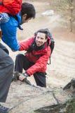Οδοιπόρος που βοηθά το φίλο πραγματοποιώντας οδοιπορικό στο δάσος στοκ φωτογραφία με δικαίωμα ελεύθερης χρήσης