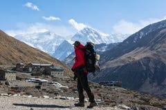 Οδοιπόρος που κοιτάζει στο χωριό Leddar και της συνόδου κορυφής Gangapurna Στοκ Φωτογραφία
