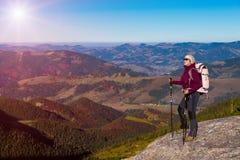 Οδοιπόρος που μένει στον υψηλό βράχο και τη θέα βουνού με φθινοπωρινό να λάμψει δασών και ήλιων Στοκ Φωτογραφίες