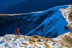 Οδοιπόρος που περπατά στα βουνά κλίσεων χιονιού που συσσωρεύονται μέσα μακριά Στοκ Εικόνες