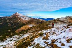 Οδοιπόρος που περπατά στα βουνά κλίσεων χιονιού που συσσωρεύονται μέσα μακριά Στοκ φωτογραφίες με δικαίωμα ελεύθερης χρήσης