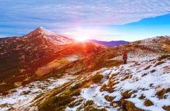 Οδοιπόρος που περπατά στα βουνά κλίσεων χιονιού που συσσωρεύονται μέσα μακριά Στοκ φωτογραφία με δικαίωμα ελεύθερης χρήσης