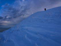 Οδοιπόρος που φθάνει στη σύνοδο κορυφής του υποστηρίγματος Catria το χειμώνα στο ηλιοβασίλεμα, Ουμβρία, Apennines, Ιταλία Στοκ Φωτογραφία