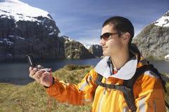Οδοιπόρος που χρησιμοποιεί την πυξίδα από τη λίμνη βουνών Στοκ Εικόνα