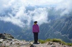 Οδοιπόρος προσώπων που στέκεται στα σύννεφα στην αιχμή βουνών Στοκ Φωτογραφία