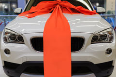 Ολοκαίνουργιο άσπρο παρόν αυτοκίνητο με τη μεγάλη κόκκινη διακόσμηση κορδελλών στοκ φωτογραφίες