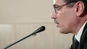 Ο ομιλητής ελέγχει το μικρόφωνο πρίν μιλά και μιλά, αντιμετωπίζει την κινηματογράφηση σε πρώτο πλάνο, πλάγια όψη απόθεμα βίντεο