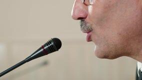 Ο ομιλητής ελέγχει το μικρόφωνο πρίν μιλά και μιλά, αντιμετωπίζει την κινηματογράφηση σε πρώτο πλάνο, πλάγια όψη φιλμ μικρού μήκους