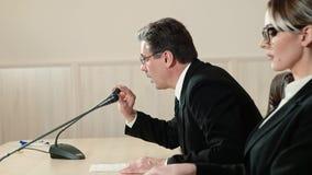 Ο ομιλητής και ο βοηθός του παίρνουν τις θέσεις τους στα μικρόφωνα, πλάγια όψη Αρχή της συνέντευξης τύπου απόθεμα βίντεο