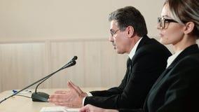 Ο ομιλητής με έναν βοηθό σε μια συνέντευξη τύπου απαντά στις ερωτήσεις από τους δημοσιογράφους, πλάγια όψη φιλμ μικρού μήκους