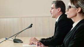 Ο ομιλητής με έναν βοηθό σε μια συνέντευξη τύπου απαντά στις ερωτήσεις από τους δημοσιογράφους, πλάγια όψη απόθεμα βίντεο