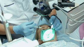 Οδοντίατρος γιατρών που χρησιμοποιεί το οδοντικό μικροσκόπιο στο οδοντικό γραφείο για τη λειτουργία ενός ασθενή γυναικών απόθεμα βίντεο