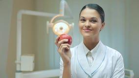 Οδοντίατρος γυναικών με το μήλο φιλμ μικρού μήκους