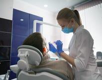Οδοντίατρος και άτομο Famele στο γραφείο οδοντιάτρων Οδοντίατρος και ασθενής Στοκ Φωτογραφία
