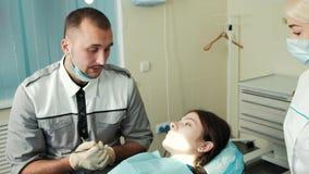 Οδοντίατρος και βοηθός που μιλούν με τον πελάτη πρίν μεταχειρίζεται απόθεμα βίντεο