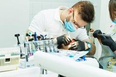 Οδοντίατρος και ο βοηθός του που πραγματοποιούν μια λεπτομερή εξέταση Στοκ Φωτογραφίες