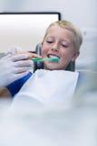 Οδοντίατρος που βοηθά το νέο ασθενή ενώ δόντια βουρτσών Στοκ Εικόνα